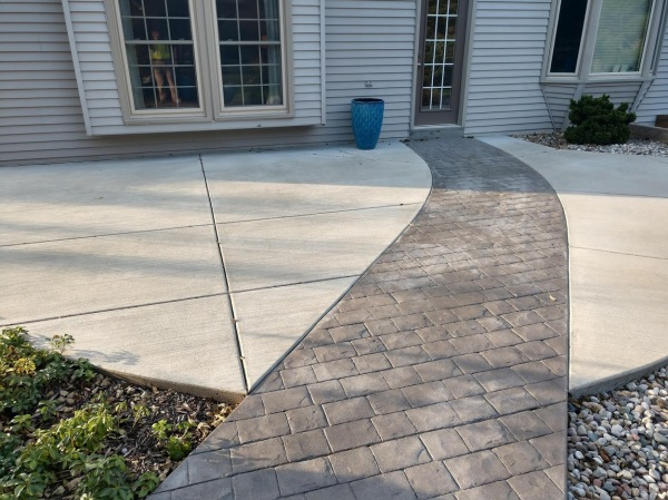 concrete patio with in laid stamped cobblestone sidewalk